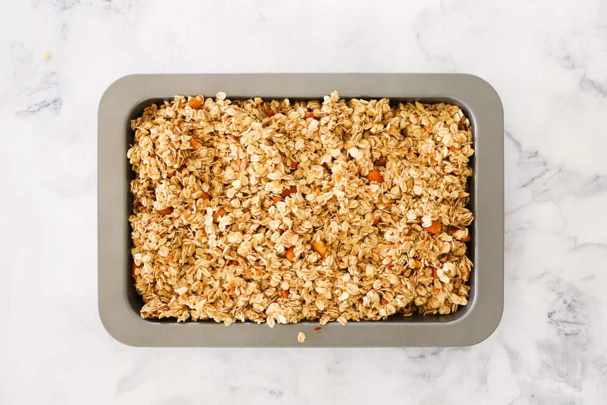 Overhead shot of mixed granola ingredients spread in a baking tin