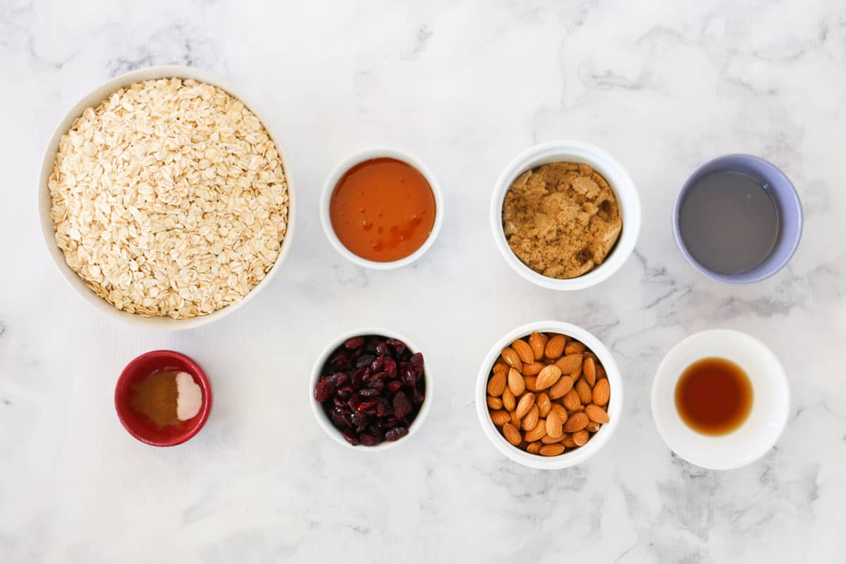 Ingredients for homemade granola in bowls on a white marble counter