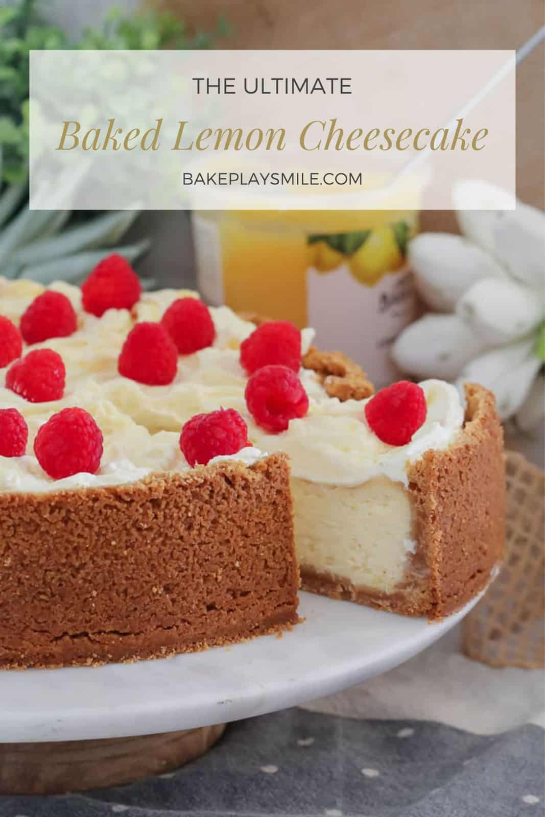 A cheesecake decorated with whipped cream and fresh raspberries on a white cake tray with one slice partly removed.
