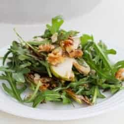 Arugula, pear and walnuts on a plate.