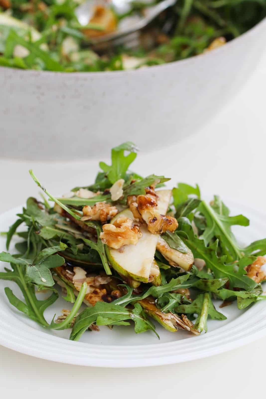 Rocket, pear and walnut salad served on a white plate.
