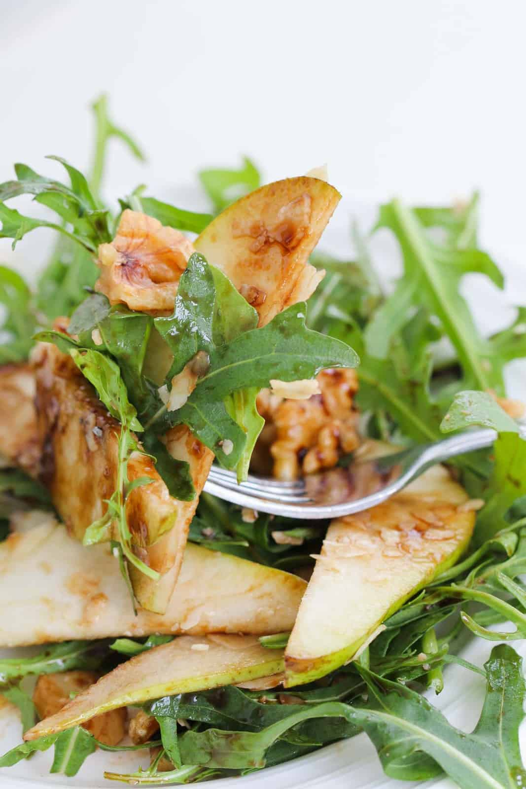 A forkful of rocket salad with pear, walnuts and parmesan.