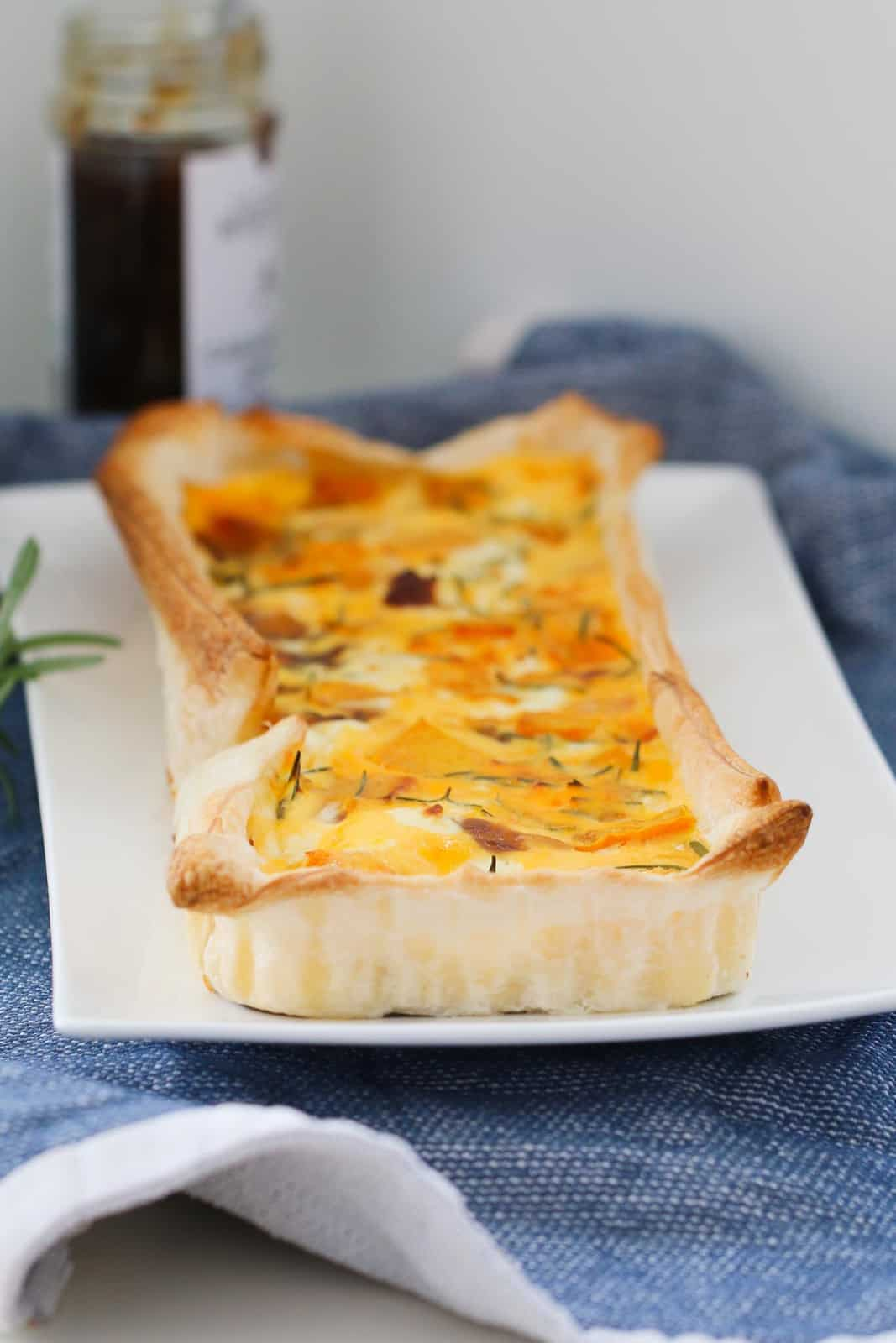 A rectangular Roast Pumpkin, Caramelized Onion & Feta Tart on a white serving dish, sitting on a blue teat towel