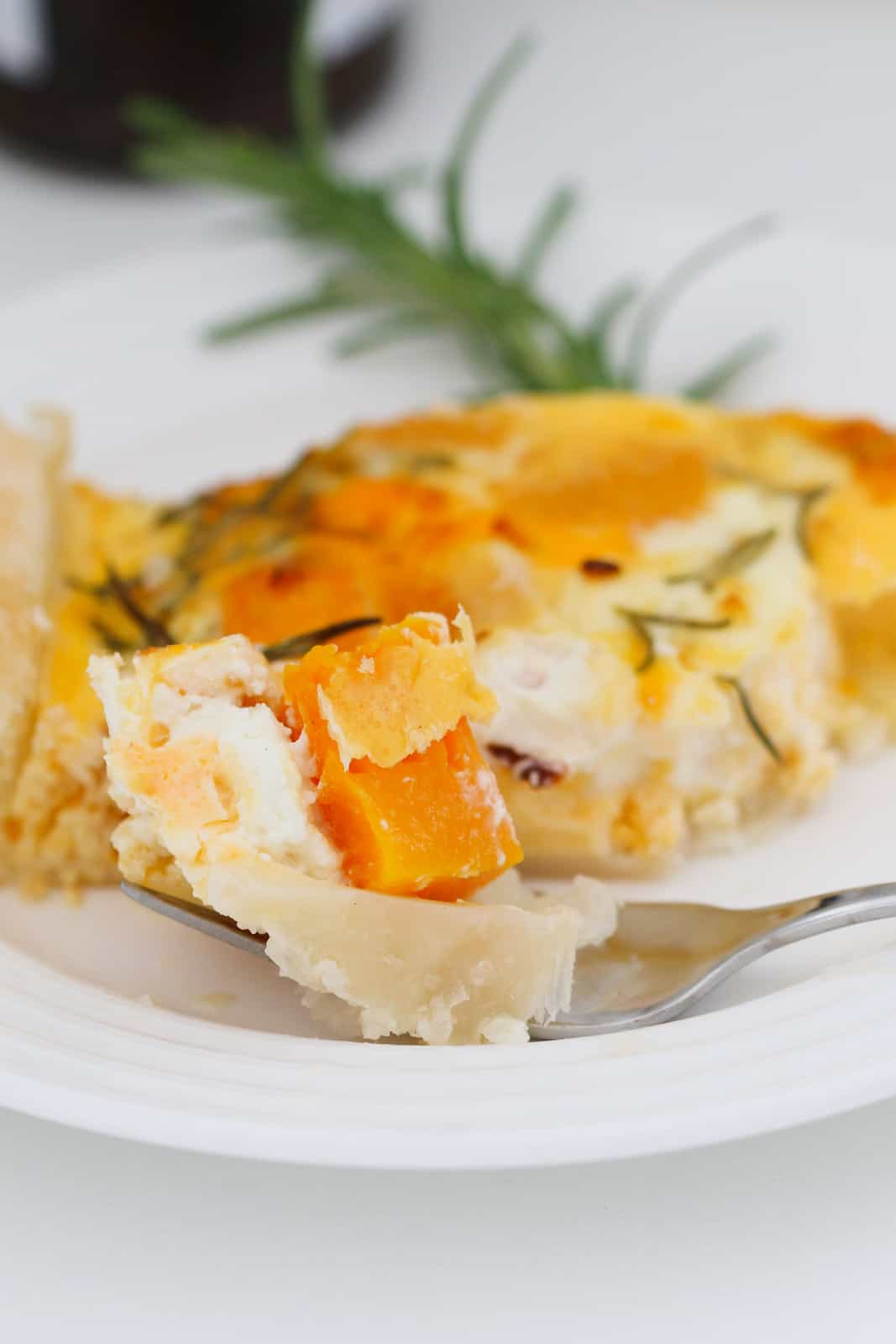 A forkful of puff pastry with pumpkin, feta and an egg filling on a plate serving of tart
