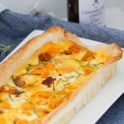 Roast Pumpkin, Caramelized Onion & Feta Tart on a serving dish with a jar of caramelized onions in the background