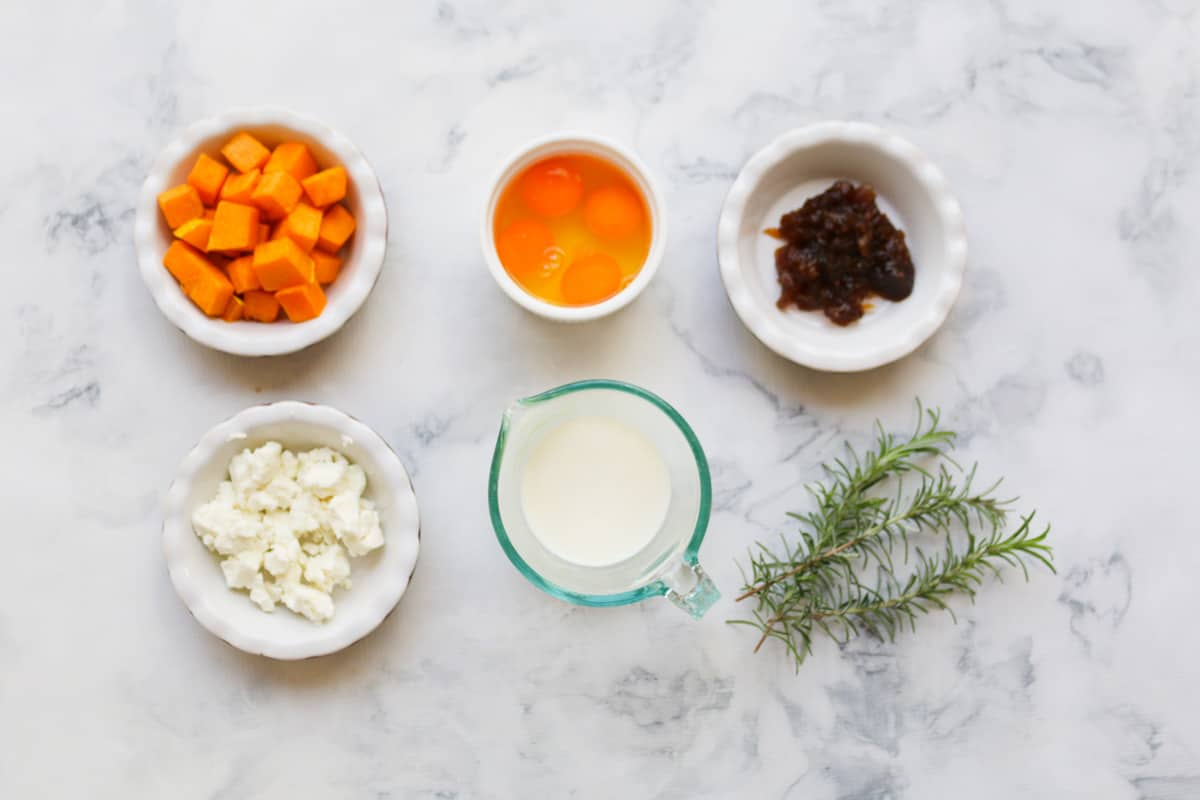 Ingredients for Roast Pumpkin, Caramelized Onion & Feta Tart in white bowls and sprigs of rosemary on a marble counter