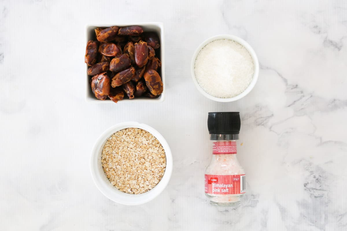 Dates in a square white bowl, desiccated coconut and oats in white bowls, and a salt shaker on a white counter top