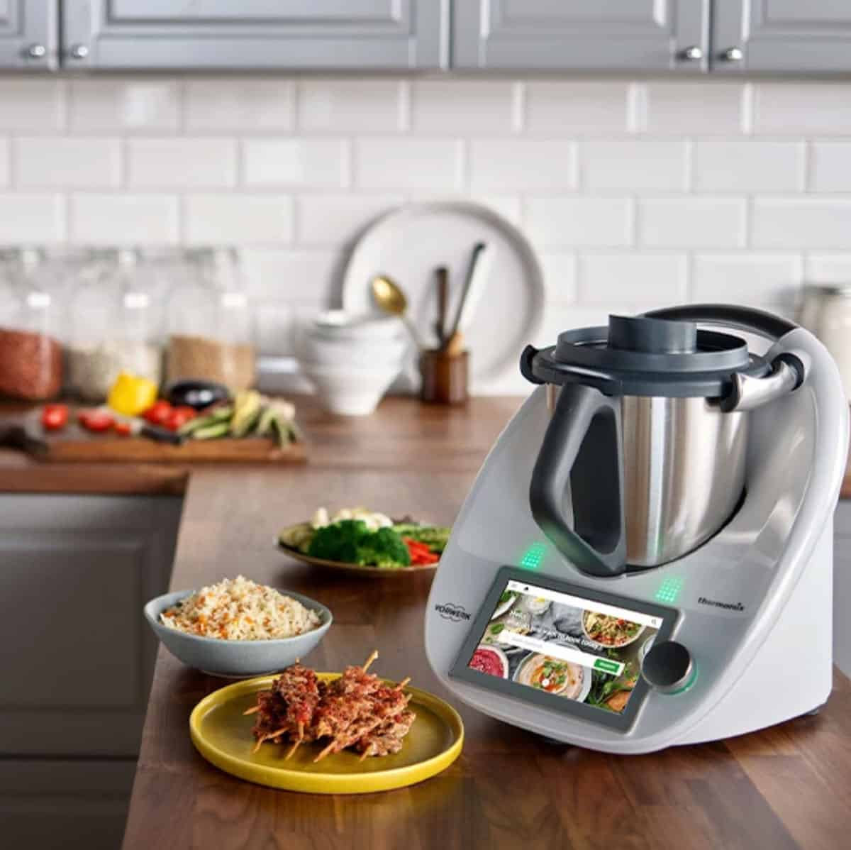 An image of a Thermomix on a kitchen bench surrounded by food.