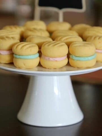 A white cake stand with yo yo biscuits that have pink and blue filling.