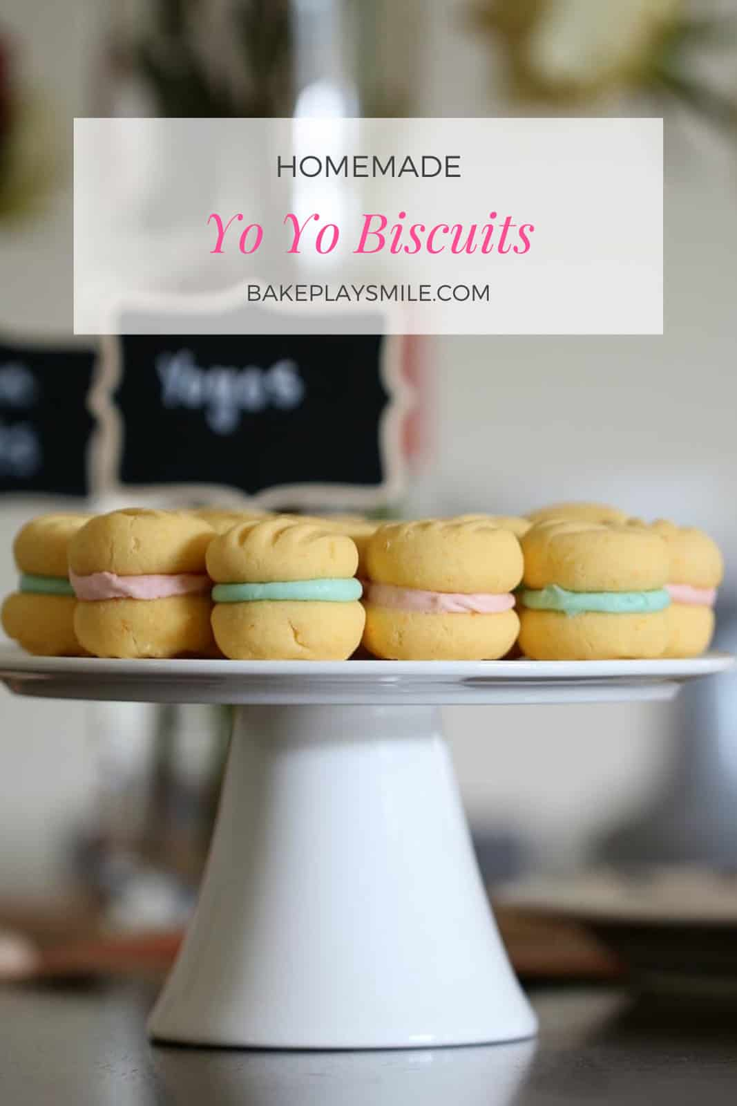 A white cake stand with yo yo biscuits that have pale pink and blue fillings.