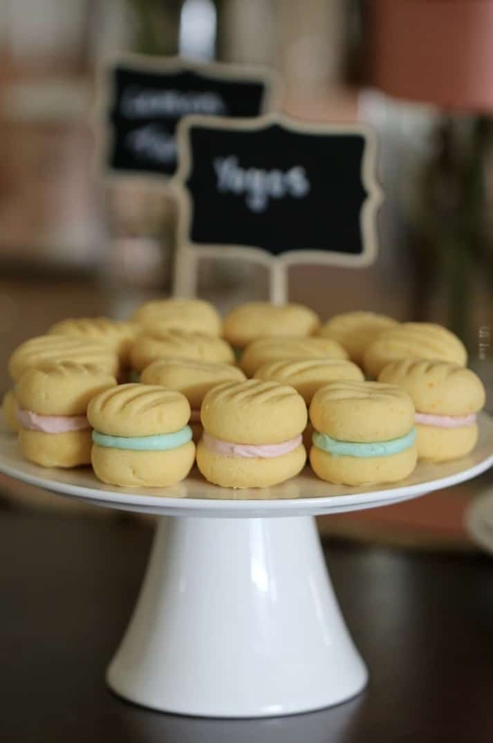 A plate of petite yo yo biscuits sandwiched together with sweet icing sugar filling on a white cake stand