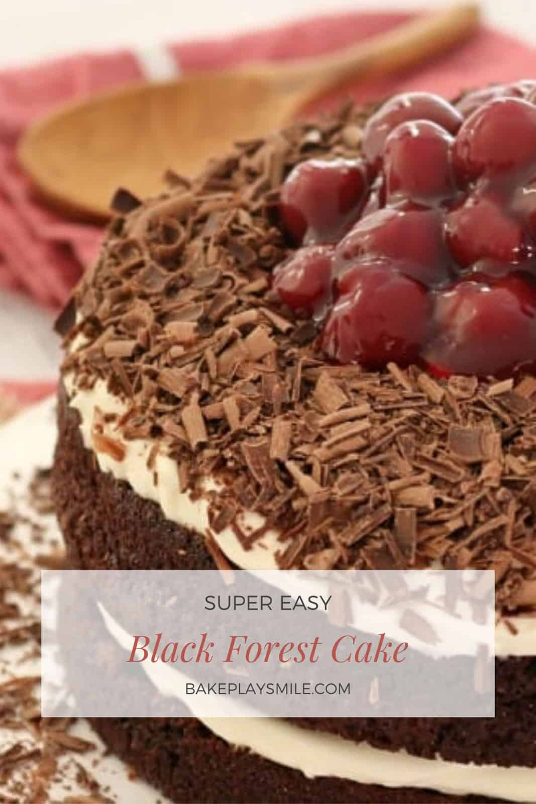 A close up of a Black Forest layered chocolate cake with whipped cream, grated chocolate and syrupy cherries piled on top.