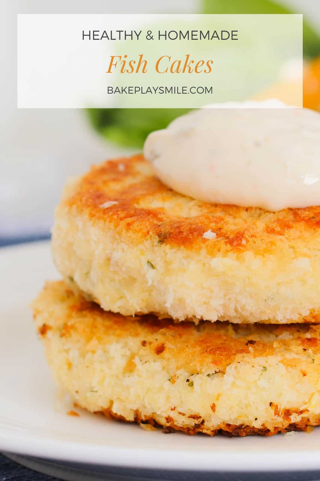 Two crispy golden fish cakes stacked with a dollop of tartare sauce on top
