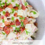 A bowl of potato salad with a creamy dressing, spring onions and bacon.