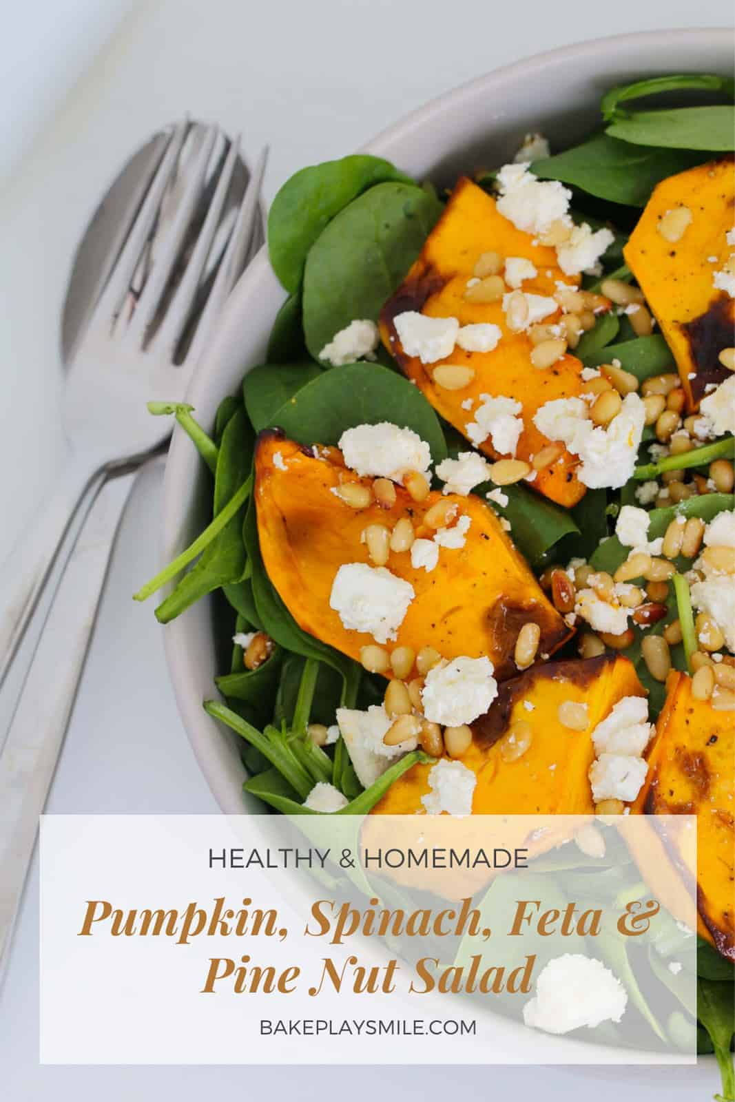 A bowl filled with baby spinach leaves, roast pumpkin slices, toasted pine nuts, crumbled feta and dressing