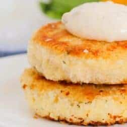 Two golden pan-fried fish cakes on a plate.