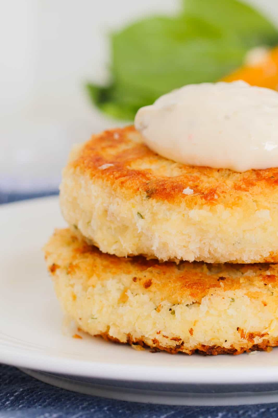Two golden pan-fried fish cakes on a plate topped with a spoonful of tartare sauce.