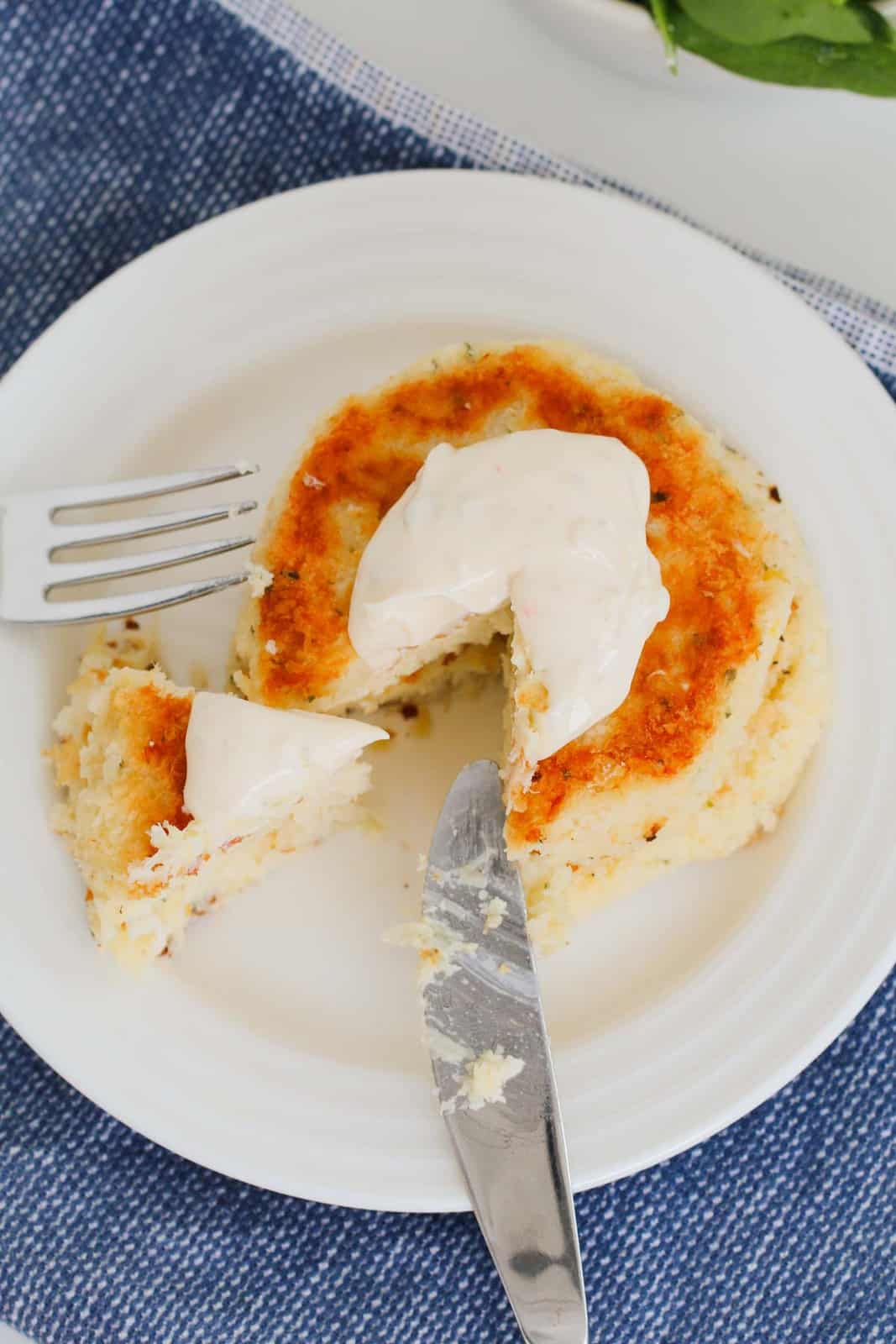 A knife and fork on a plate, with cut golden fish cakes and a dollop of aioli on top.