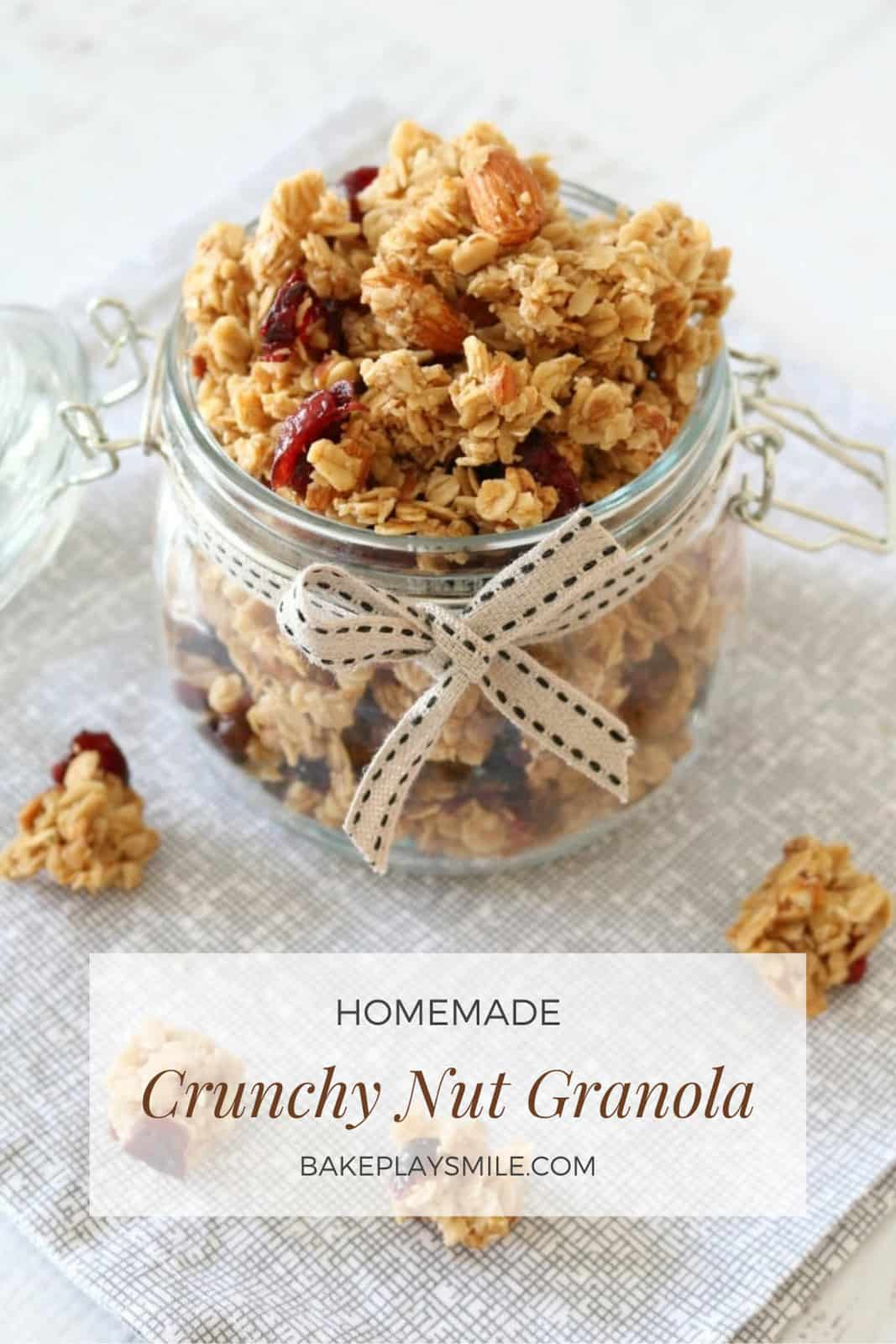 A glass jar with a ribbon tied around it, filled with fruit and nut granola clusters.