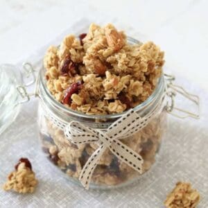 A glass jar filled with fruit and nut granola clusters.