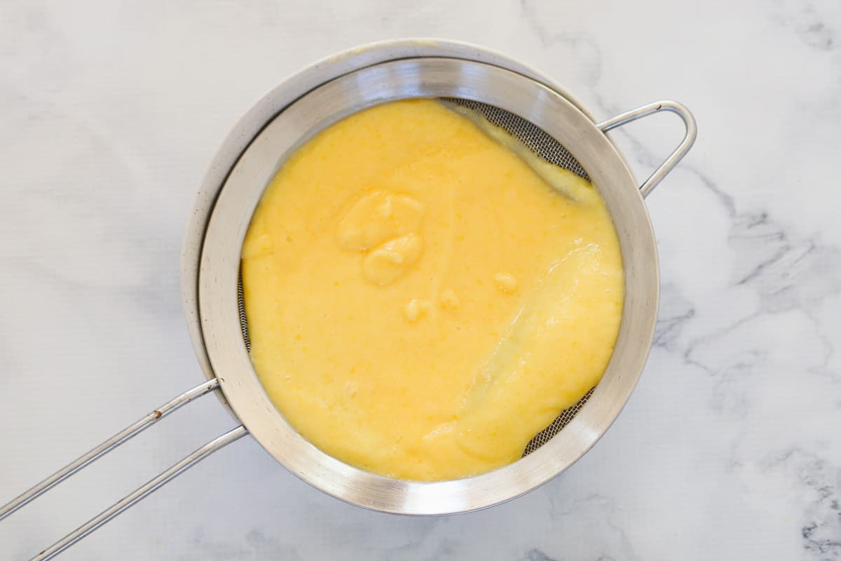 A small sieve filled with homemade lemon curd.