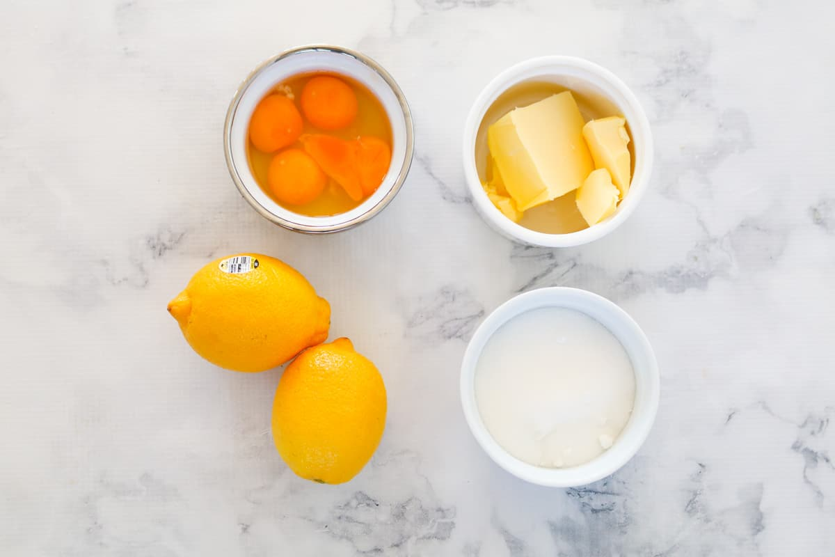 The ingredients for homemade lemon curd on a marble bench.