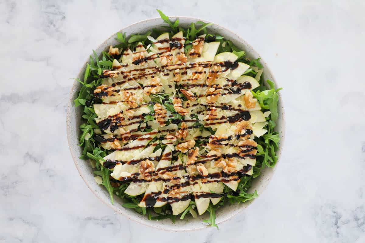 Balsamic vinegar drizzled over walnuts, pear, parmesan and rocket in a bowl.