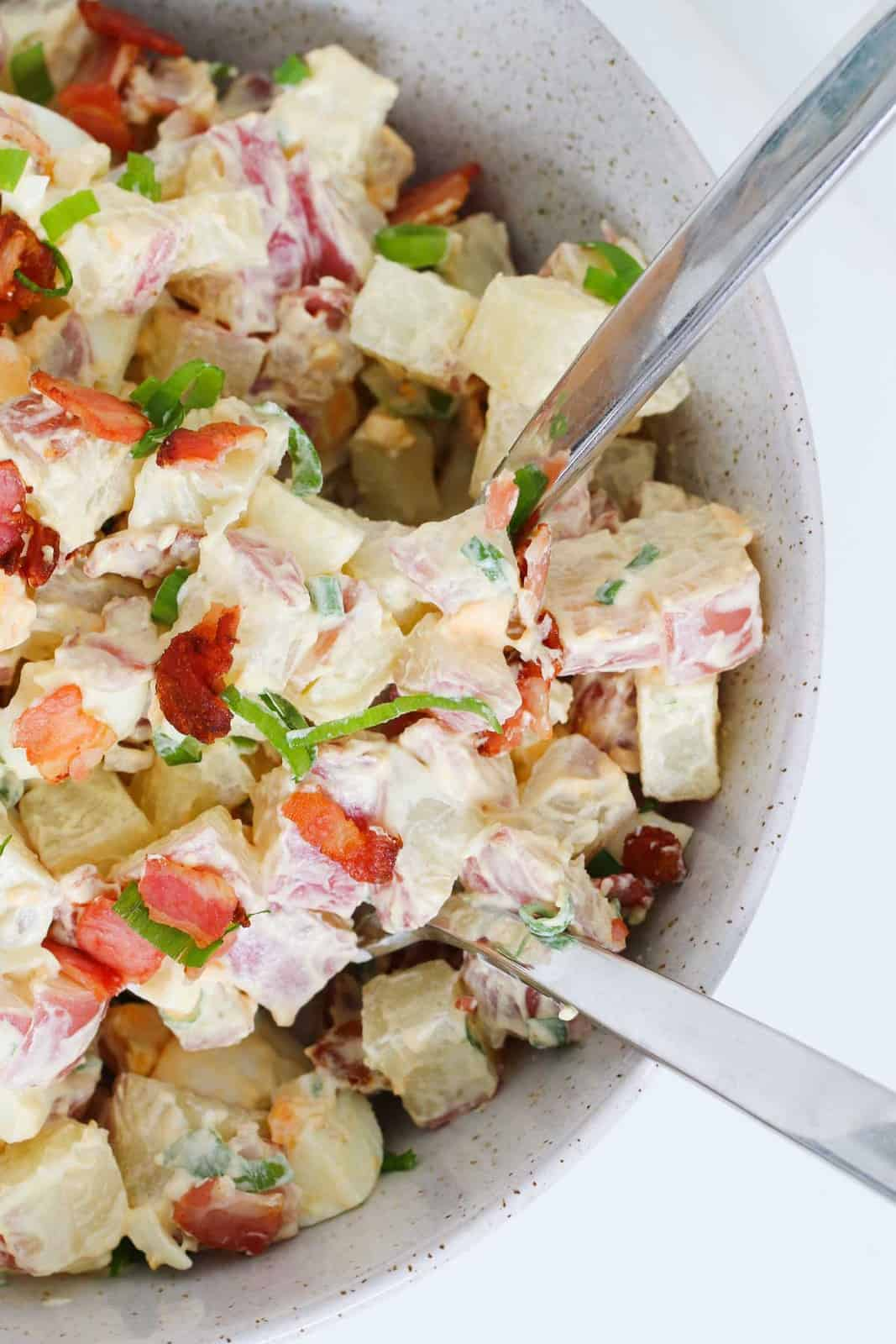 Salad servers in a bowl of potatoes, bacon, eggs, spring onions with a creamy dressing.