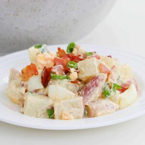 A white plate topped with chopped potatoes, egg, bacon and spring onions.