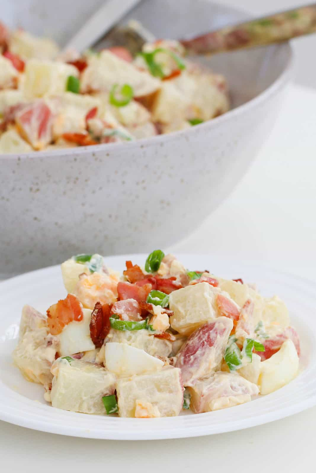 A plate of potato salad with egg, bacon and spring onions, and a bowl of potato salad in the background
