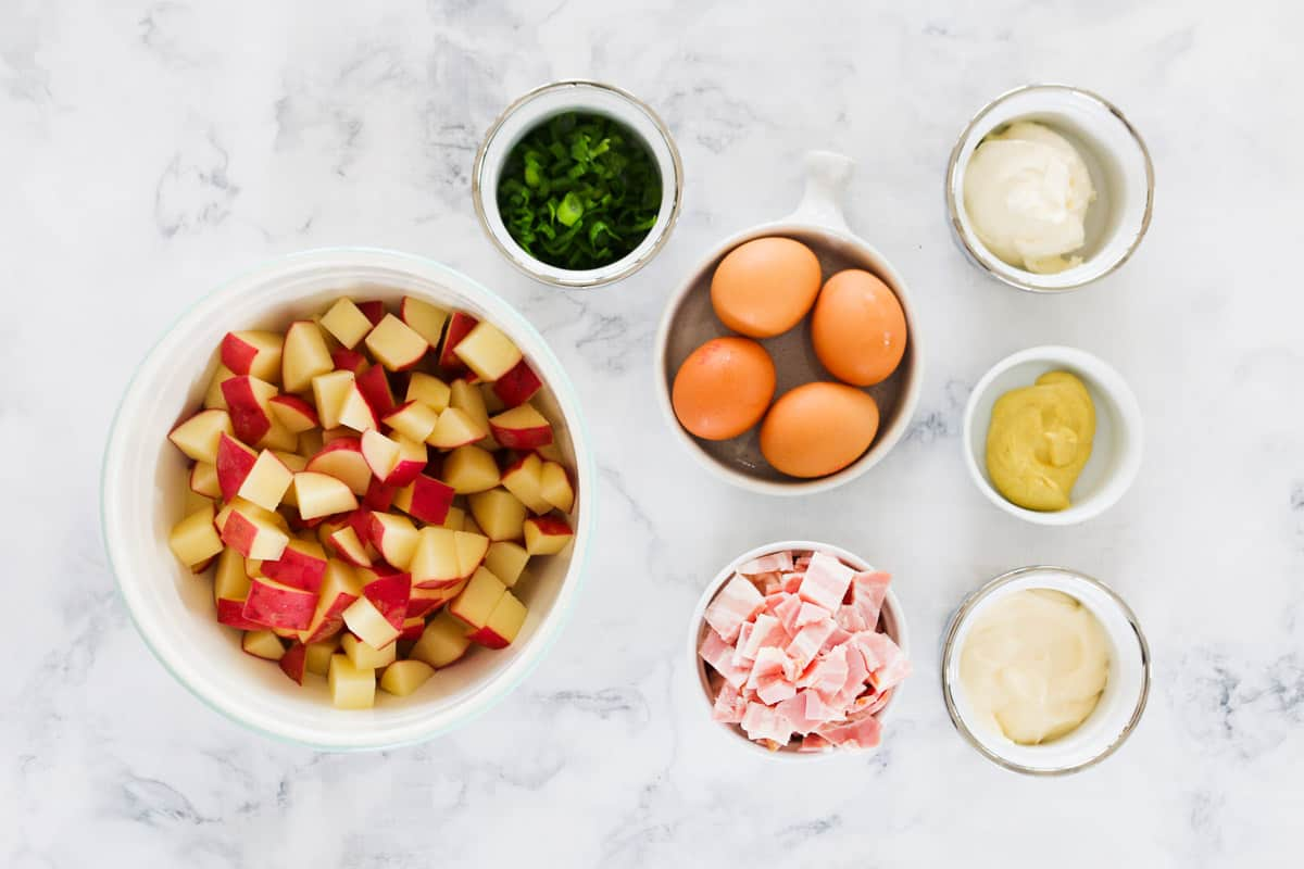 All the ingredients for potato salad in individual bowls on a marble bench