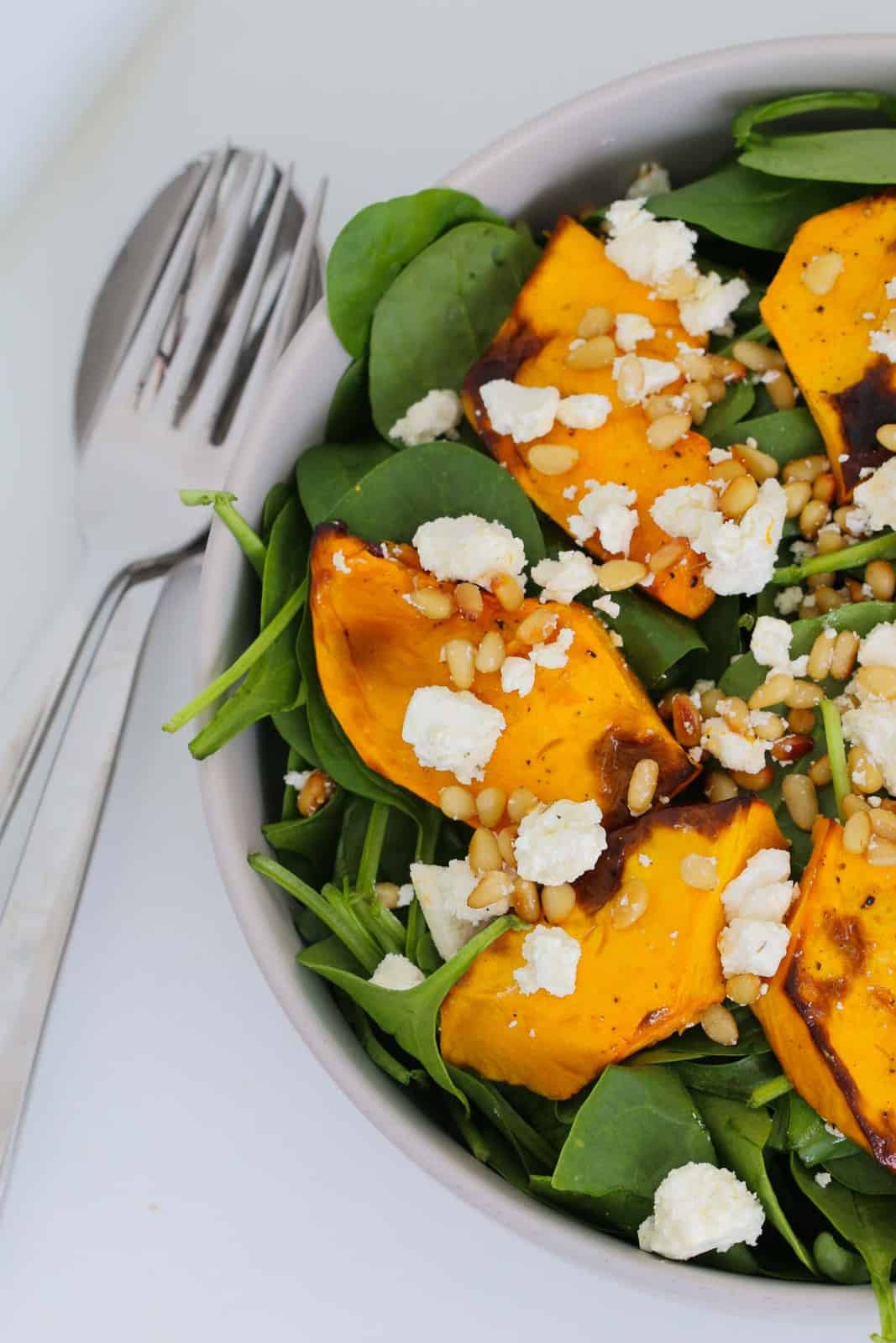 Salad servers next to a bowl of pumpkin and spinach salad, with pine nuts and feta mixed through.