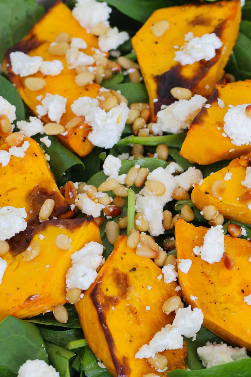 A close up of crumbled feta, pine nuts, pumpkin and spinach leaves tossed together