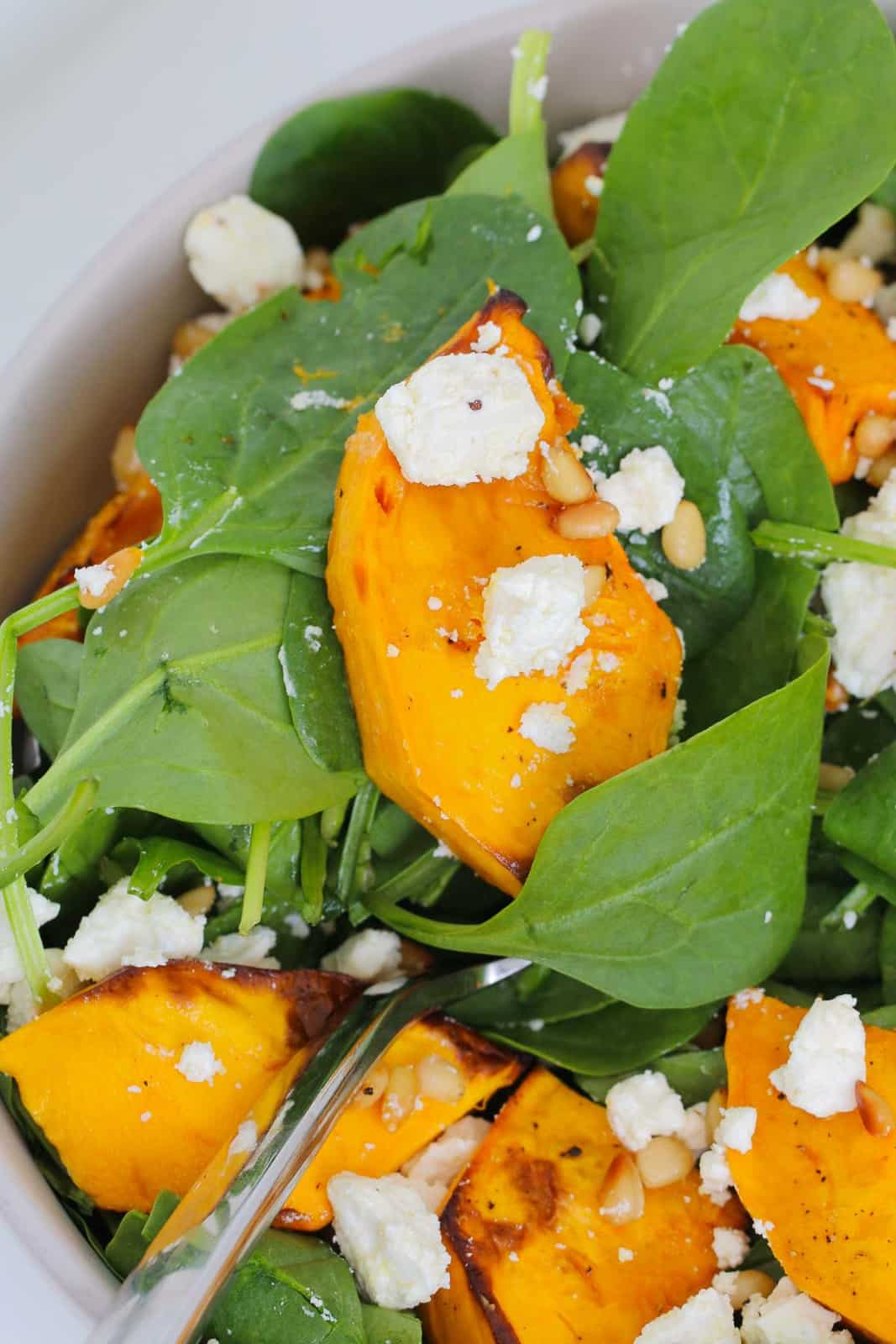 A close up shot of roasted pumpkin with baby spinach leaves, toasted pine nuts and crumbled feta in a bowl.