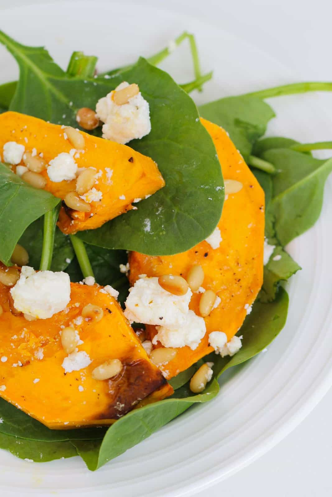 A white plate topped with roasted pumpkin slices, feta, spinach and pine nuts.