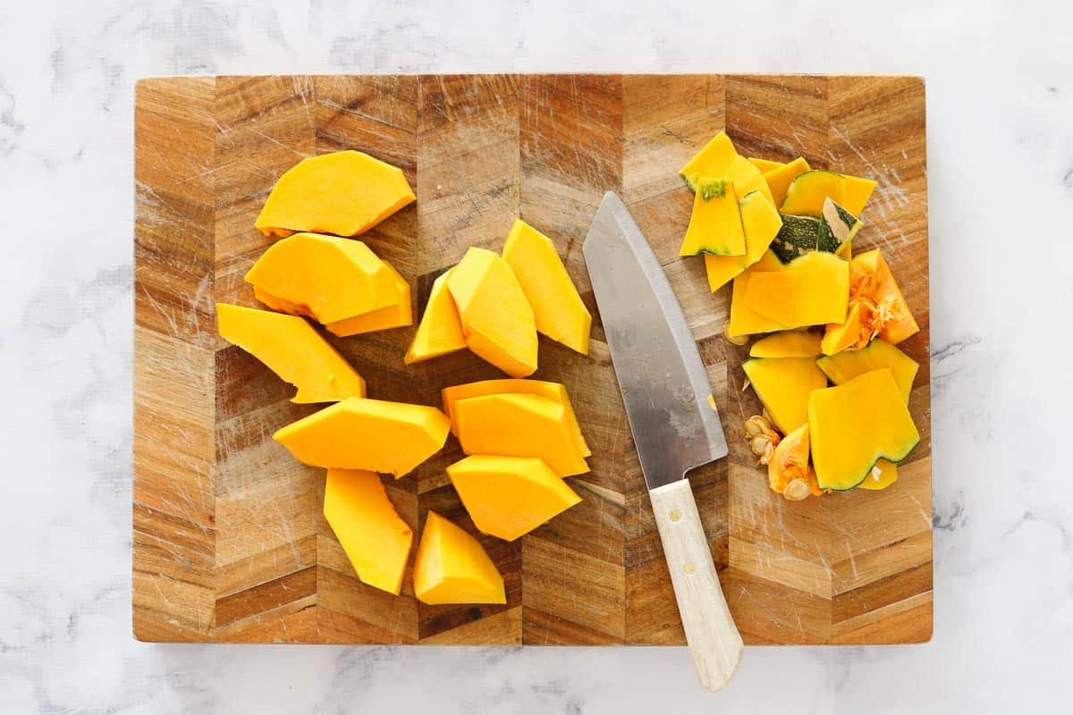 A wooden chopping board with a knife and pieces of pumpkin.