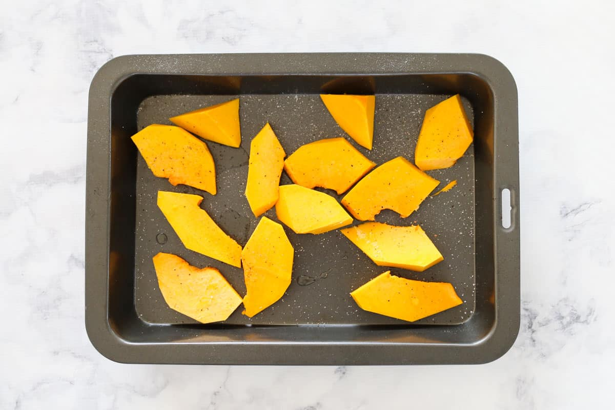 Large slices of pumpkin on a roasting tray.