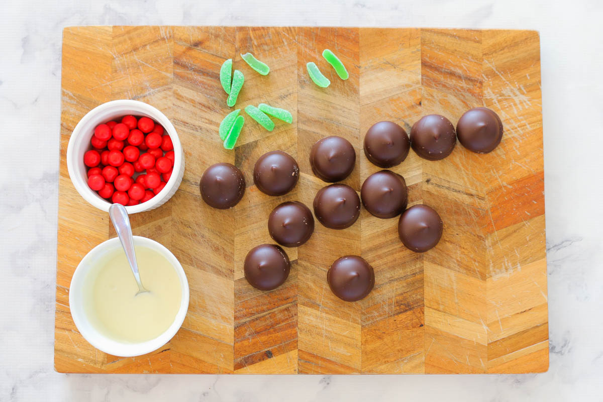 Chopped spearmint candy next to a bowl of red round chocolates, melted white chocolate and round chocolate coated marshmallow biscuits.
