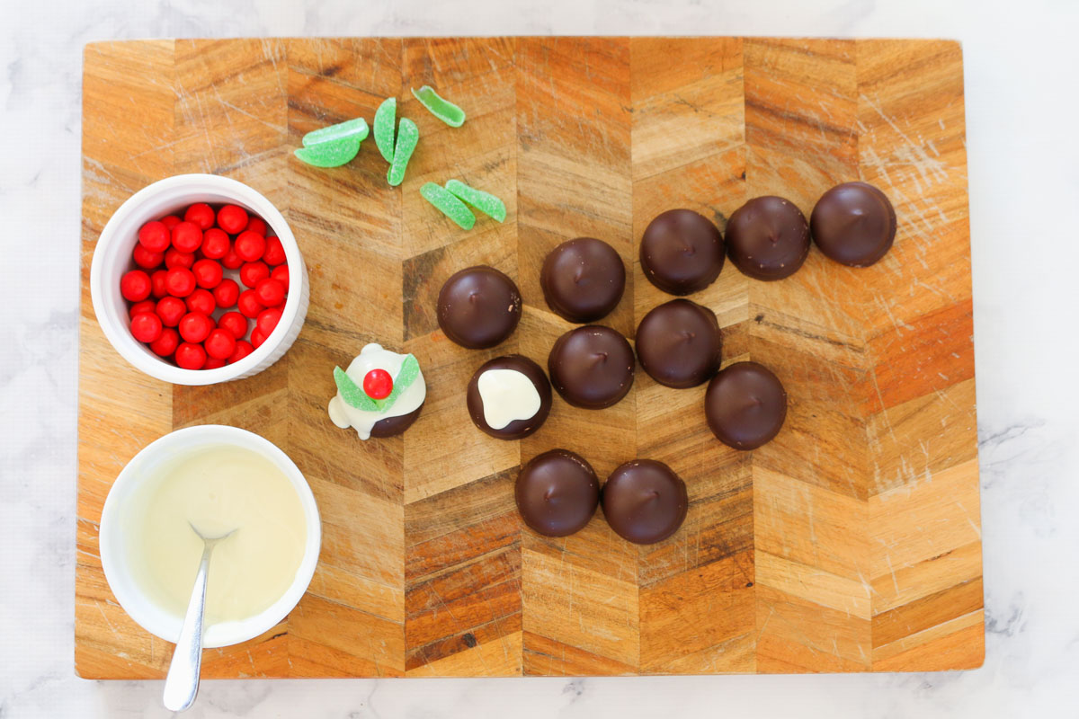 A chopping board with chocolate marshmallow biscuits, Jaffas, spearmint leaves and melted white chocolate.