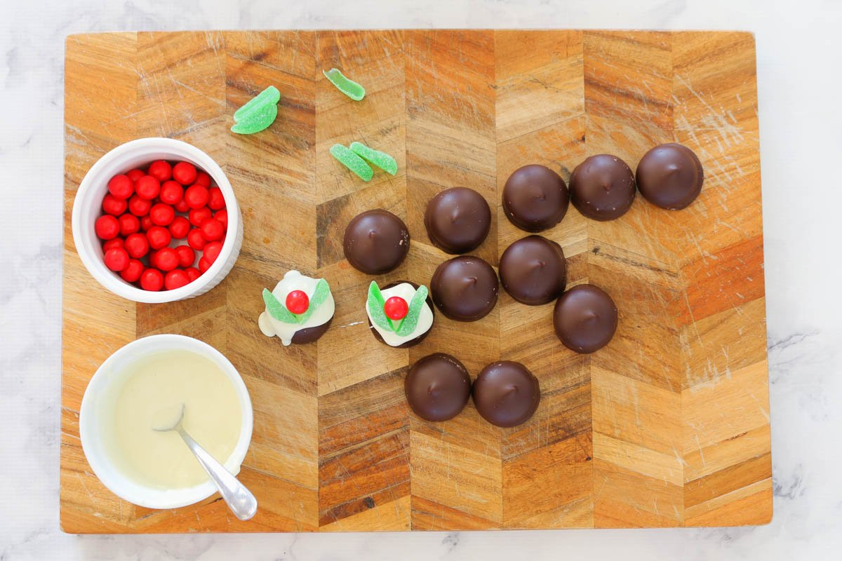 A chopping board with the ingredients to make Christmas puddings with chocolate coated marshmallow biscuits.