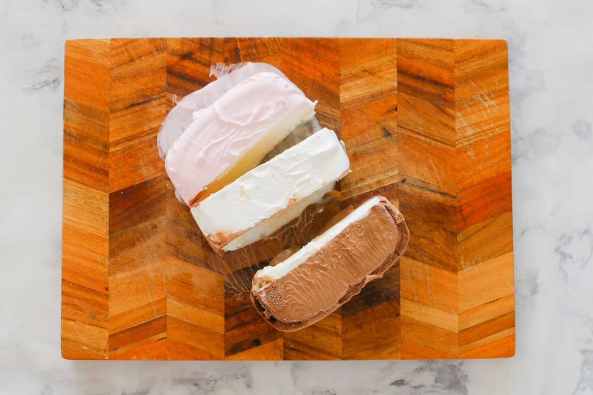 A wooden chopping board with neapolitan ice-cream being cut into three different flavours.