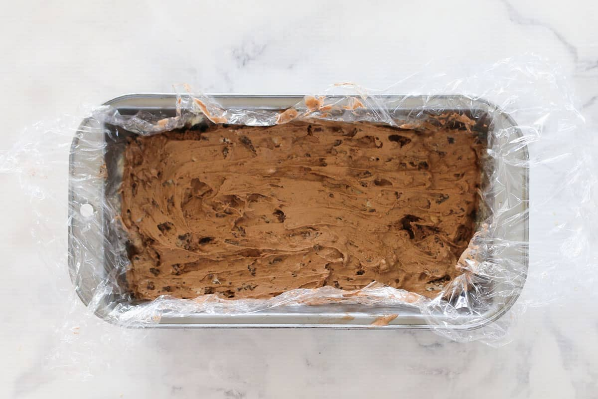 Chocolate ice-cream with Oreos mixed through in a lined rectangular loaf tin.