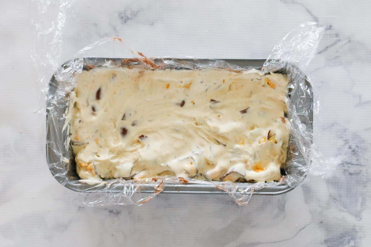 A rectangular lined loaf tin filled with vanilla ice-cream and chunks of honeycomb.