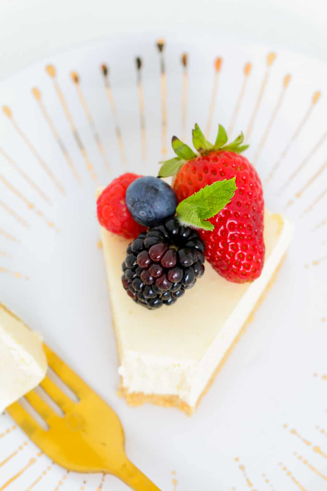 An overhead shot of a piece of white cheesecake with berries on top.