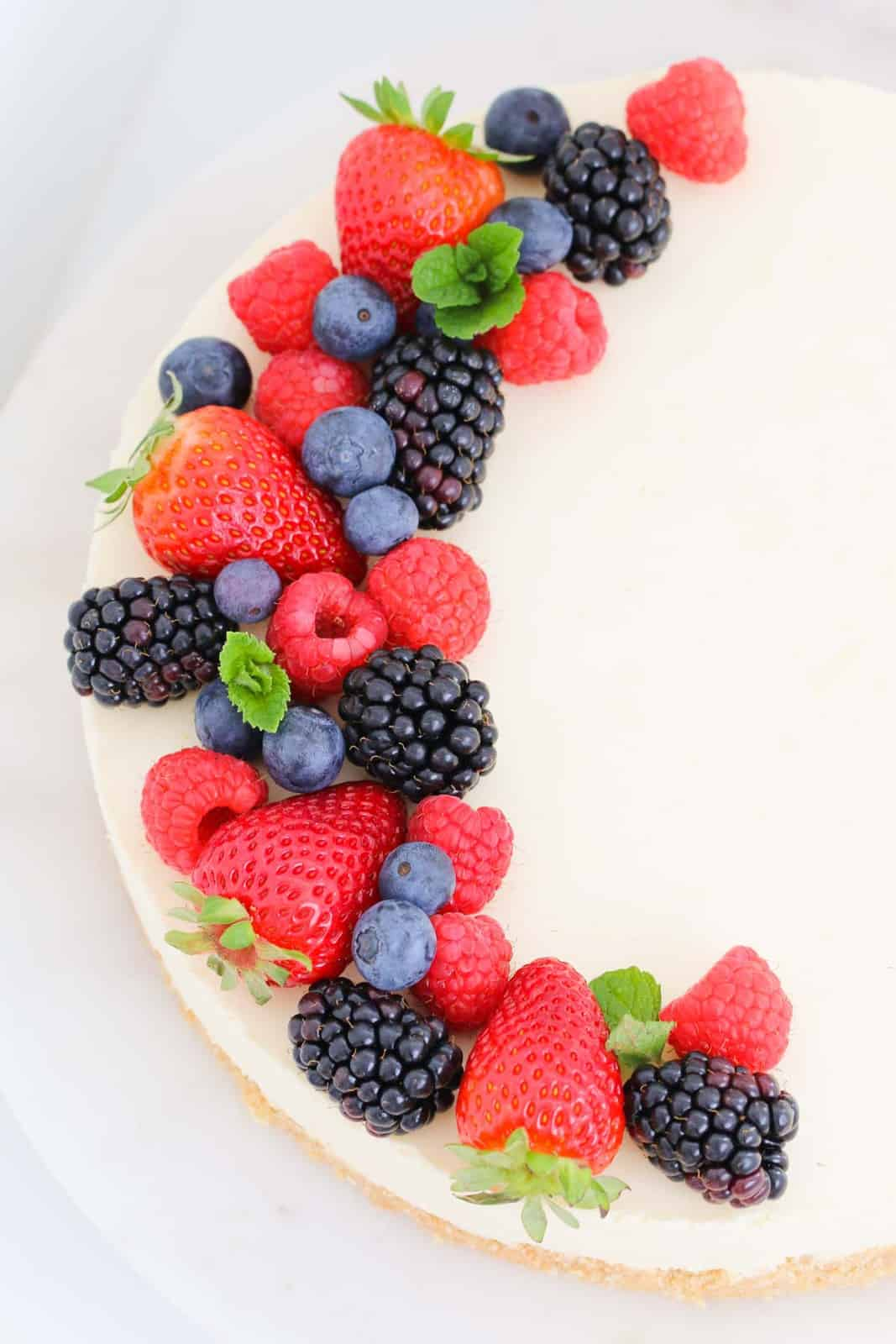 An overhead shot of fresh berries on top of a lemon cheesecake.