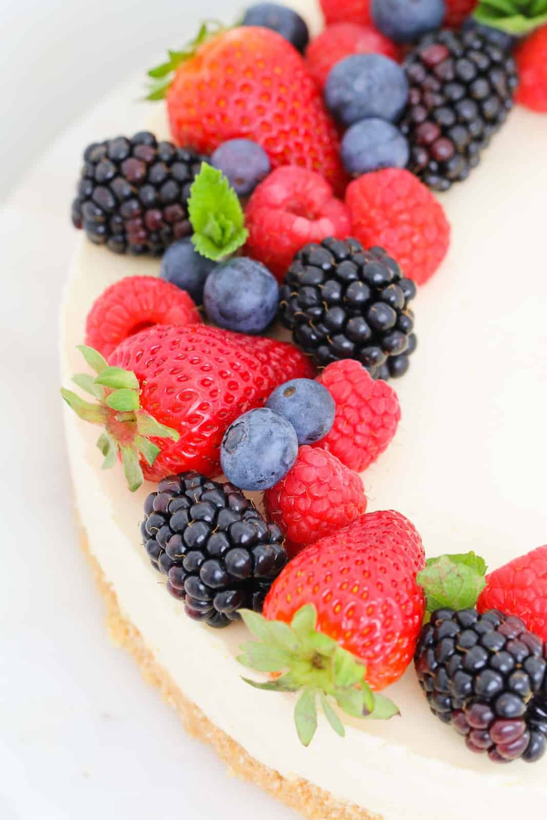 A no bake lemon cheesecake decorated with fresh berries.