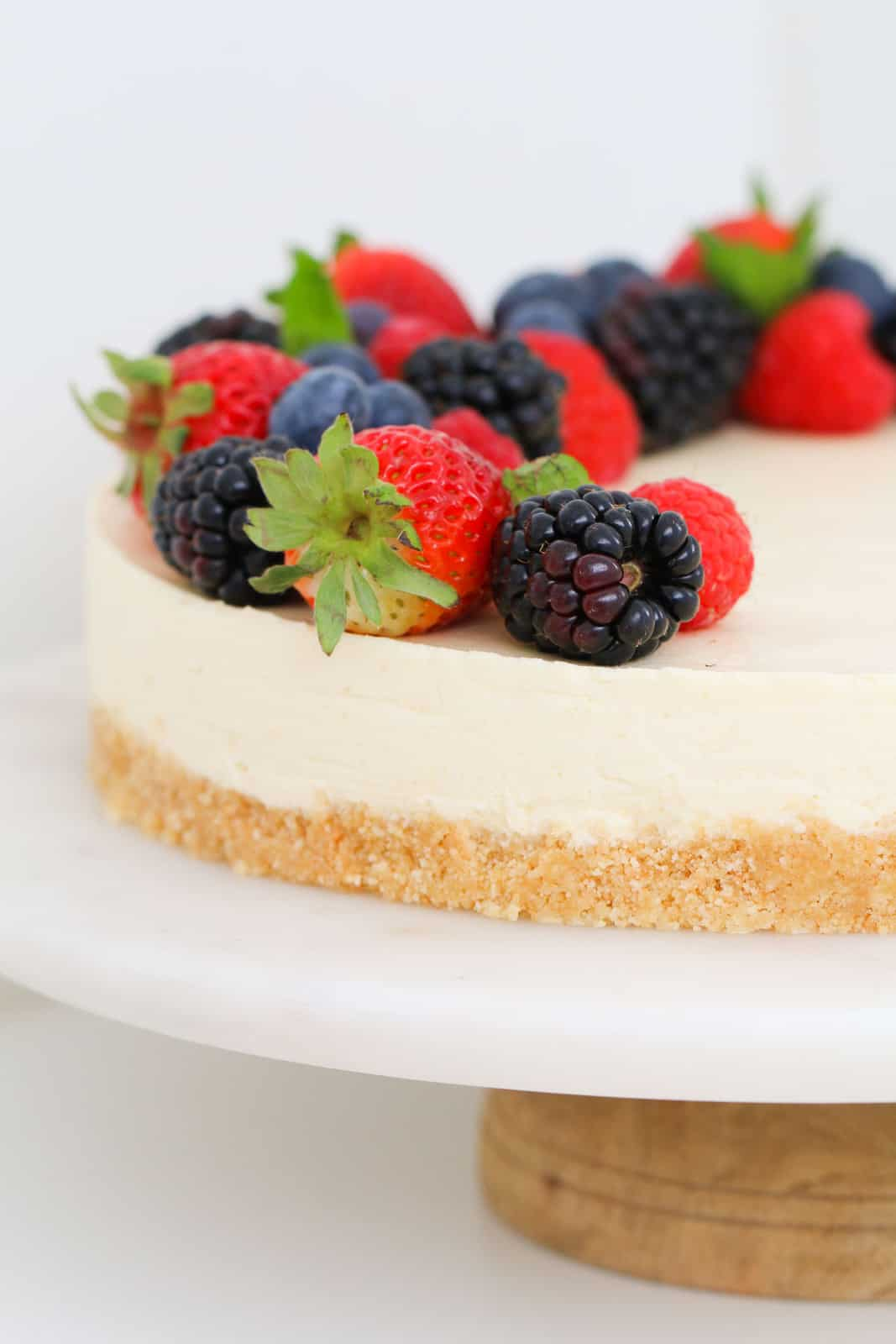 A cookie crumb lemon cheesecake on a cake stand with berries.