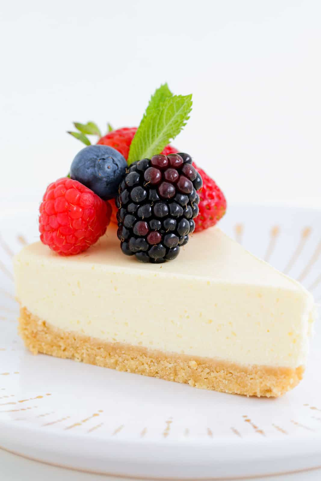 A slice of lemon cheesecake on a white plate with berries.