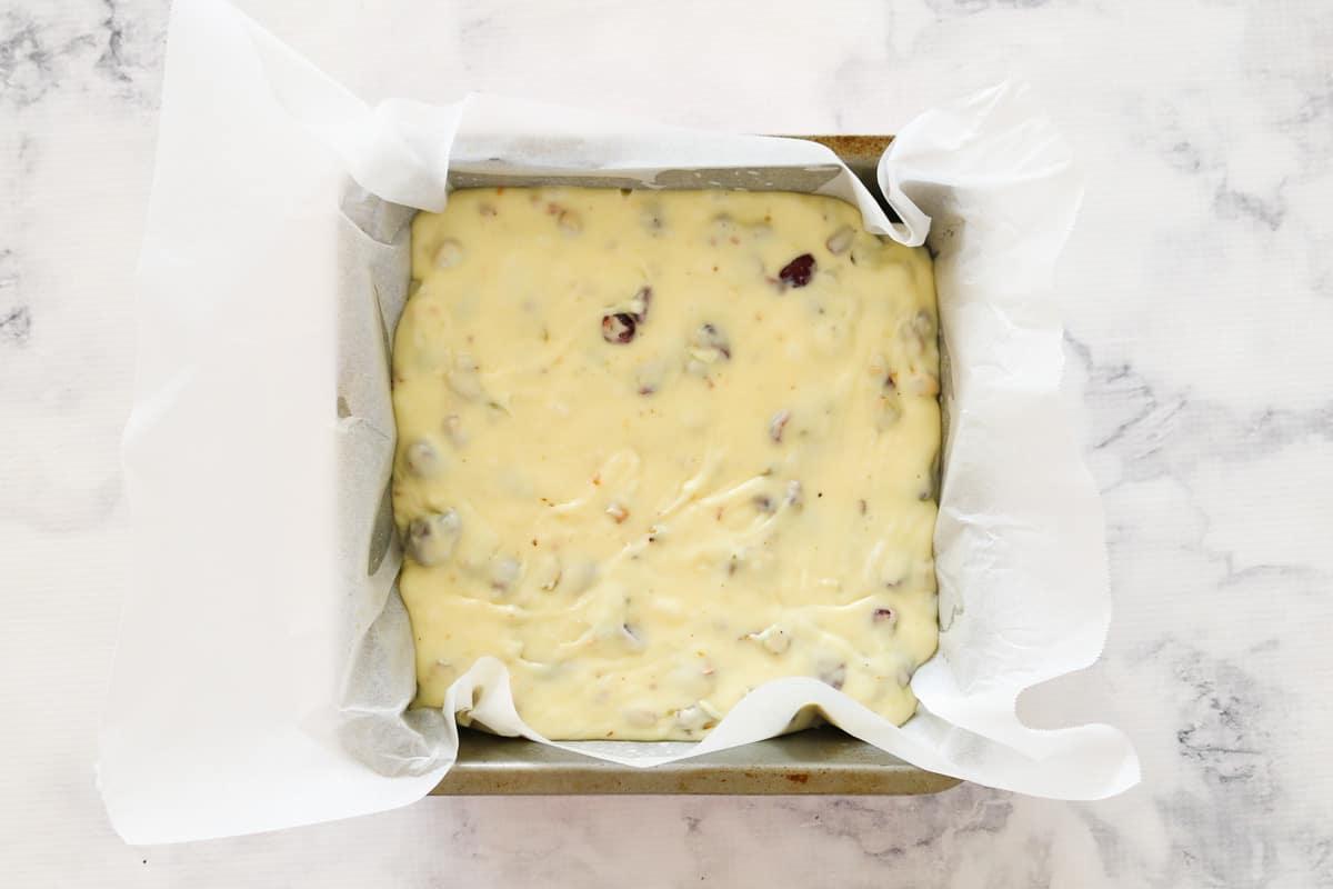 White chocolate Christmas fudge setting in a square baking tin.