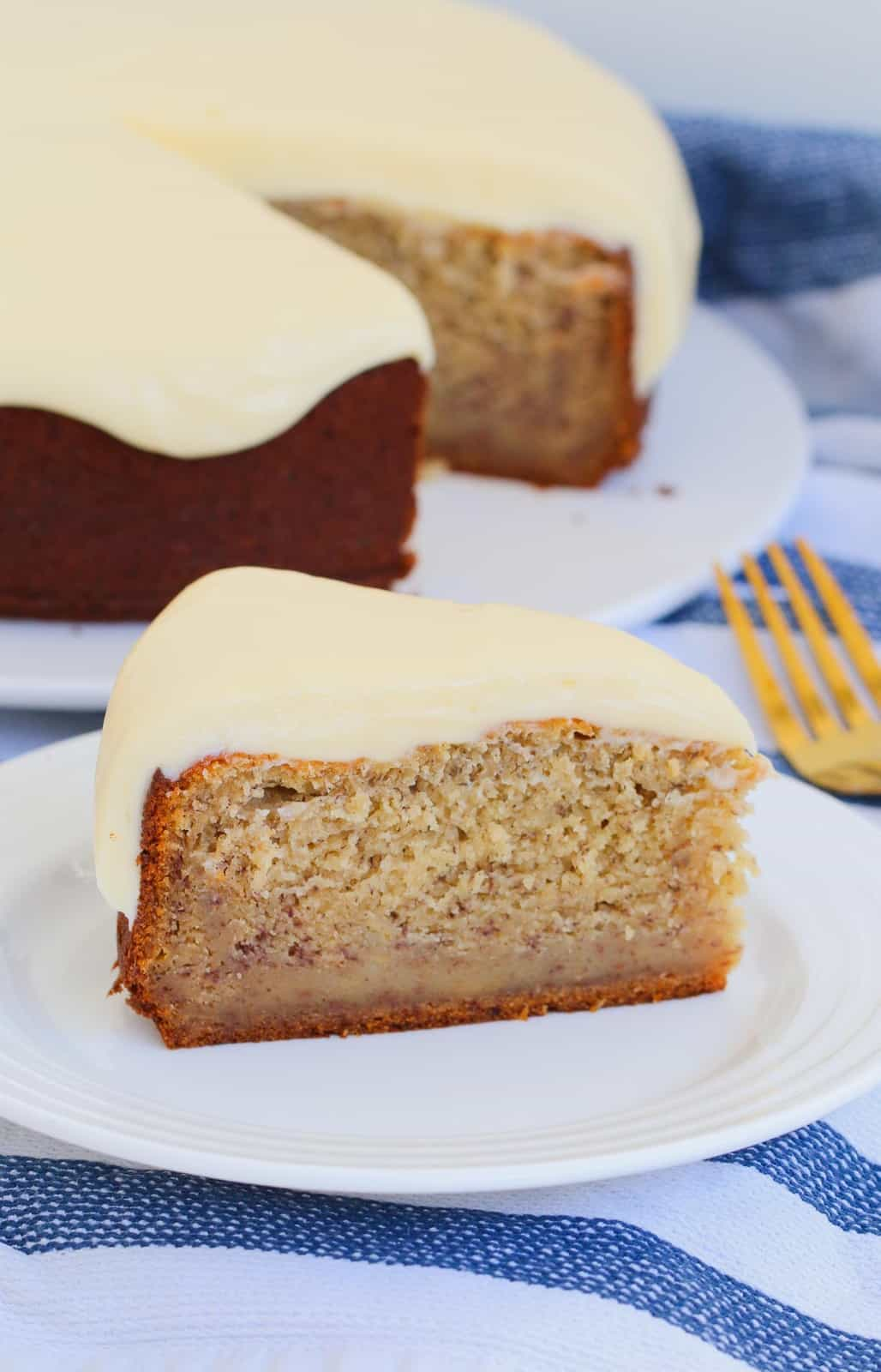 Cream cheese frosting on top of a slice of banana cake.